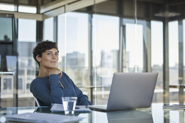 Smiling businesswoman sitting at desk in office with laptop - RBF06909