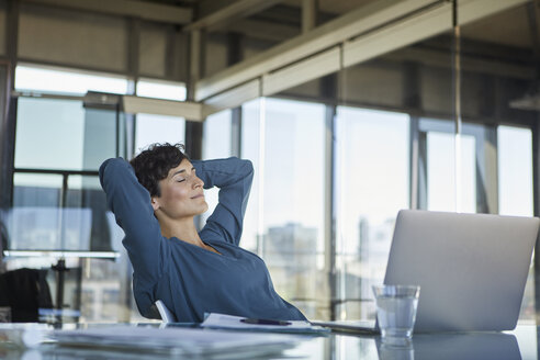 Businesswoman sitting at desk in office with closed eyes - RBF06912