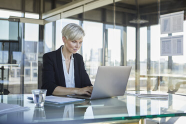 Businesswoman sitting at desk in office using laptop - RBF06915