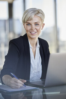 Portrait of confident businesswoman sitting at desk in office with laptop - RBF06918