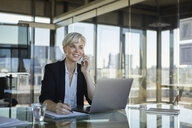 Smiling businesswoman working at desk in office - RBF06924