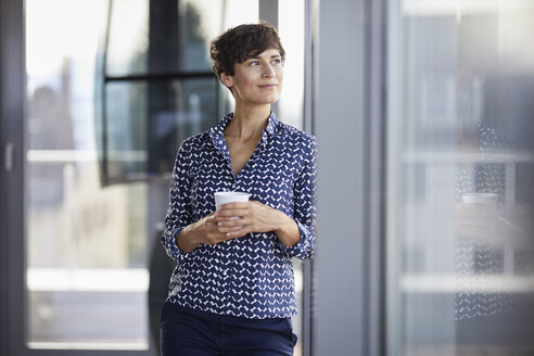 Smiling businesswoman in office looking out of window - RBF06933