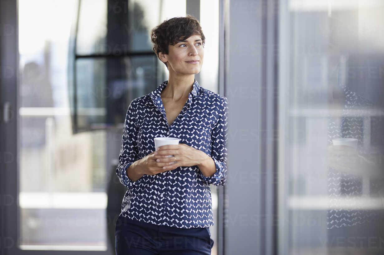 Smiling businesswoman in office looking out of window - RBF06933 - Rainer Berg/Westend61