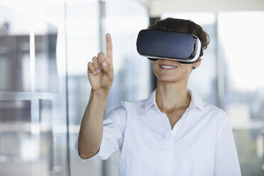 Businesswoman wearing VR glasses in office raising her finger - RBF06939