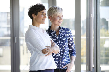 Two smiling businesswomen looking out of window in office - RBF06954