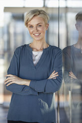 Portrait of smiling woman leaning against window - RBF06972