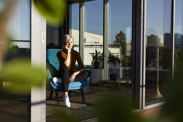 Woman sitting in armchair looking out of window - RBF06978