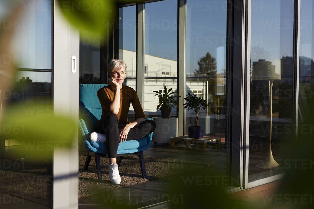 Woman sitting in armchair looking out of window - RBF06978 - Rainer Berg/Westend61