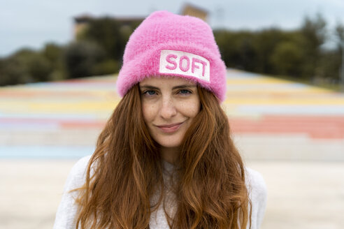 Portrait of redheaded woman wearing pink cap with the word 'soft' - AFVF02177