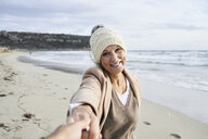 Senior lady pulling friend at the beach in winter wearing hat and coat. Come with me. Menorca, Spain. - IGGF00700
