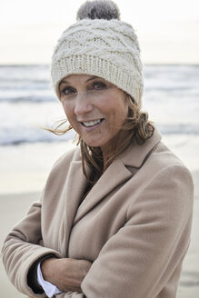 Spain, Menorca, portrait of smiling senior woman wearing bobble hat on the beach in winter - IGGF00706