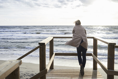Spain, Menorca, back view of senior woman standing on boardwalk in winter looking at the sea - IGGF00715