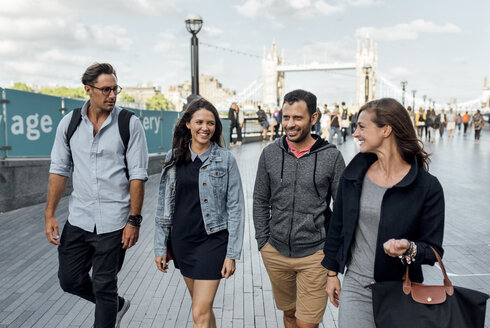 UK, London, happy friends walking near   Tower Bridge - MGOF03900