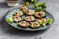 Baked aubergine slices spread with walnut creme garnished with pomegranate seeds - SARF04029