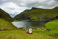 Denmark, Faroe islands, Streymoy, Woman with her daughter looking to fjord of Saksun - RUNF00559