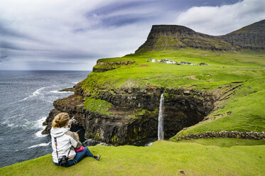 Denmark, Faroe islands, Vagar, Woman and her daughter looking at the Gasadalur waterfall - RUNF00562