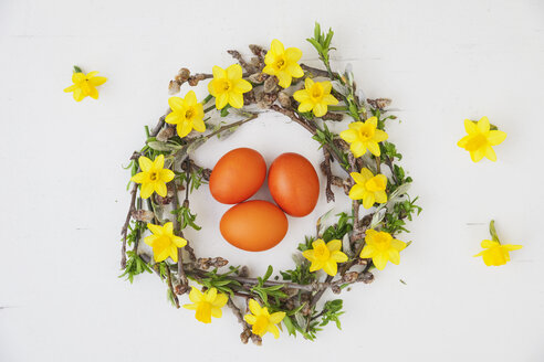 Self-made Easter wreath and orange dyed eggs on white ground - GWF05749