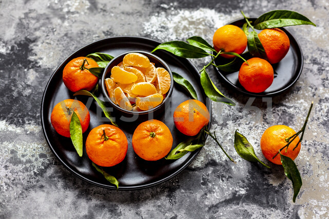Tangerines with leaves, on plate and pieces in bowl - SARF04041