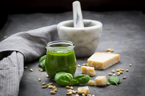 Glass of homemade pesto Genovese, ingredients, mortar and kitchen towel - LVF07620