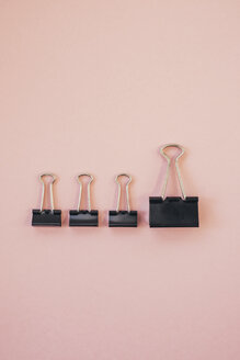 Black paper clips against pink background - MOMF00573