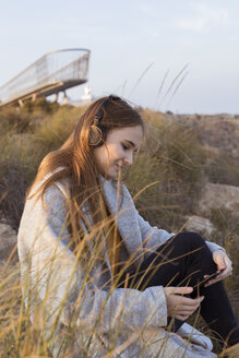 Spain, Alicante, Santa Pola, Cape Santa Pola, young woman sitting on rock at sunset listening to music on her cell phone - GRSF00039