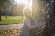 Young girl embracing tree in autumn - LVF07627