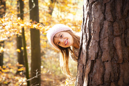 Young girl behind tree in autumn - LVF07630