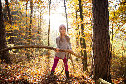 Young girl holding branch in autumn forest - LVF07633