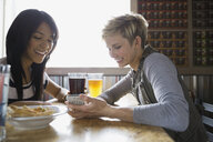 Women text messaging with cell phone at brewery - HEROF03407