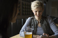 Woman text messaging with cell phone in brewery - HEROF03413
