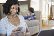 Woman using cell phone in living room - HEROF03419