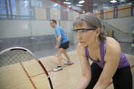 Serious woman playing squash on indoor court - HEROF03536