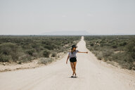 Namibia, woman hitchhiking on the road to Spitzkoppe - LHPF00338