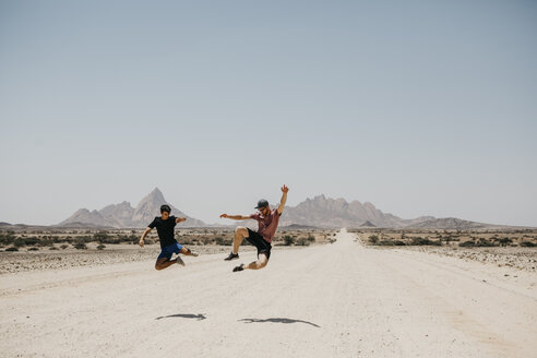 Namibia, two friends jumping on the road to Spitzkoppe - LHPF00341