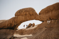 Namibia, Spitzkoppe, two friends jumping at rock formation - LHPF00347