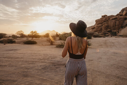 Namibia, Spitzkoppe, rear view of woman with hat at sunset - LHPF00362