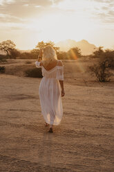 Namibia, Spitzkoppe, rear view of woman walking in desert landscape at sunset - LHPF00365