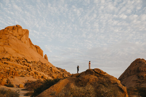 Namibia, Spitzkoppe, couple standing on a rock at sunset - LHPF00368