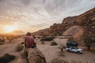 Namibia, Spitzkoppe, friends sitting on a rock watching the sunset - LHPF00371