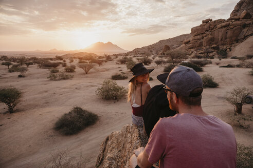 Namibia, Spitzkoppe, friends sitting on a rock at sunset - LHPF00374