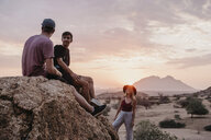 Namibia, Spitzkoppe, friends sitting on a rock at sunset - LHPF00380