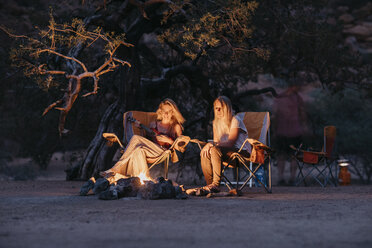 Namibia, friends sitting at campfire playing guitar - LHPF00383