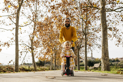 Father and daughter enjoying a morning day in the park in autumn, girl on scooter - JRFF02253