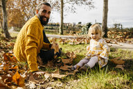 Father and daughter sitting on meadow with autumn leaves, morning day in the park - JRFF02259