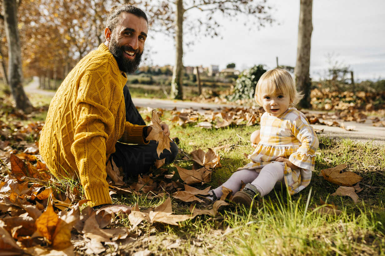 Father and daughter sitting on meadow with autumn leaves, morning day in the park - JRFF02259 - Josep Rovirosa/Westend61