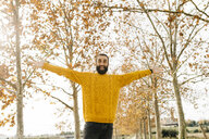 Young man with open arms and happy in a park in autumn - JRFF02262