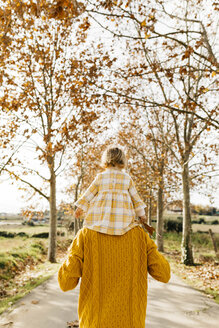 Father carrying his little daughter on shoulders in the morning, park in autumn - JRFF02265