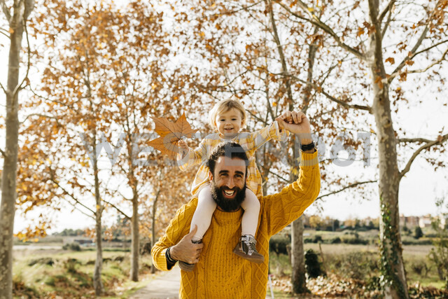 Father carrying his little daughter on shoulders on a morning day in the park in autumn - JRFF02268 - Josep Rovirosa/Westend61