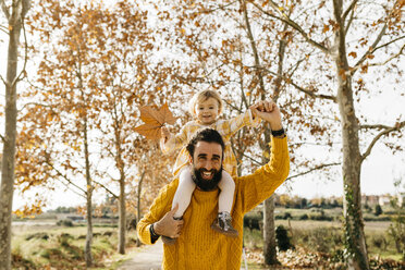 Father carrying his little daughter on shoulders on a morning day in the park in autumn - JRFF02268