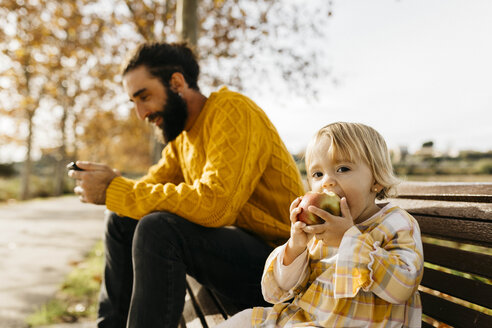 Father and daughter sitting on a bench in the park in autumn, father using smartphone, daughter eating an apple - JRFF02274